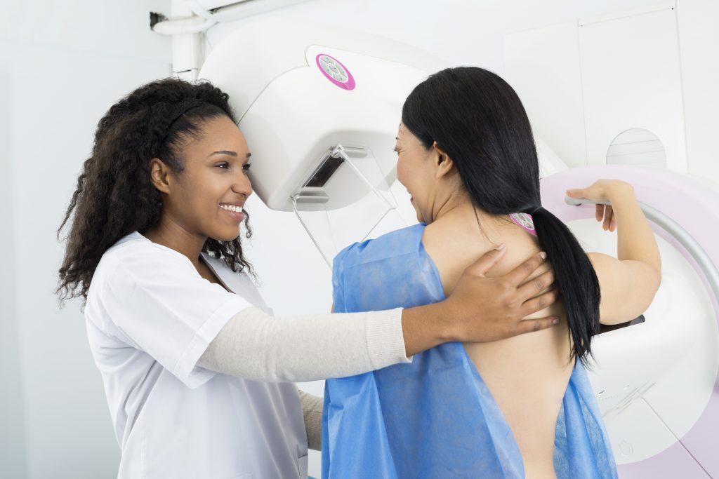 Nurse Helping Woman Undergoing Mammogram X-ray Test
